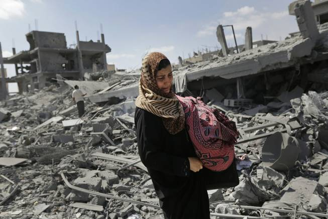 A Palestinian woman carries her belongings past the rubble of houses destroyed by Israeli strikes in Beit Hanoun, northern Gaza Strip, Saturday, July 26, 2014. Thousands of Gaza residents who had fled Israel-Hamas fighting streamed back to devastated border areas during a lull Saturday and were met by large-scale destruction: scores of homes were pulverized, wreckage blocked roads and power cables dangled in the streets.