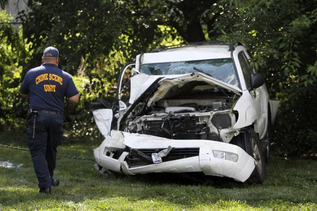 An investigator examines a heavily damaged SUV before it is towed from the scene of a fatal accident in North Philadelphia on Friday, July 25, 2014. Two children were killed and three people critically injured when a hijacked car lost control and hit a group of people near a fruit stand, according to police.