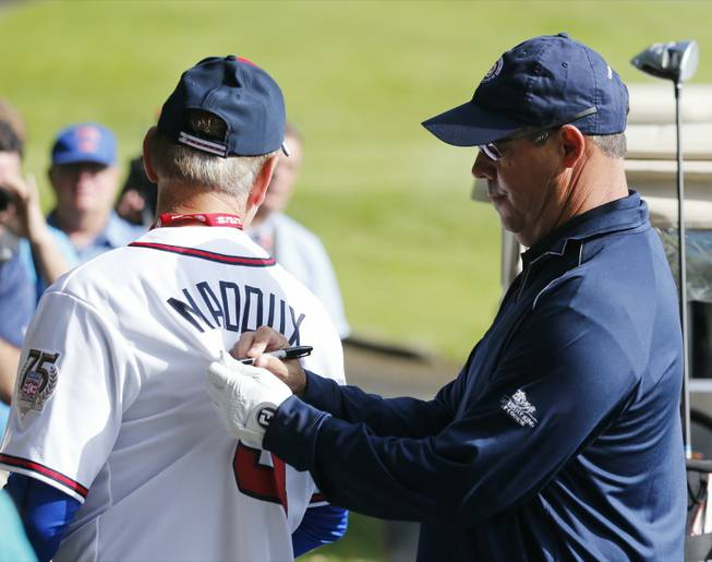 Former Atlanta Braves and Chicago Cubs pitcher Greg Maddux signs an autograph during a baseball Hall of Fame golf outing at Leatherstocking Golf Course on Saturday, July 26, 2014, in Cooperstown, N.Y.