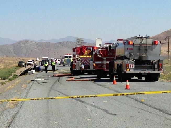 Emergency personnel work at the site of a collision between a pickup truck and a small airplane that was making an emergency landing on Nevada Route 445, about 20 miles north of Reno, on Saturday, July 26, 2014. Police said all four occupants of both vehicles escaped with minor injuries.
