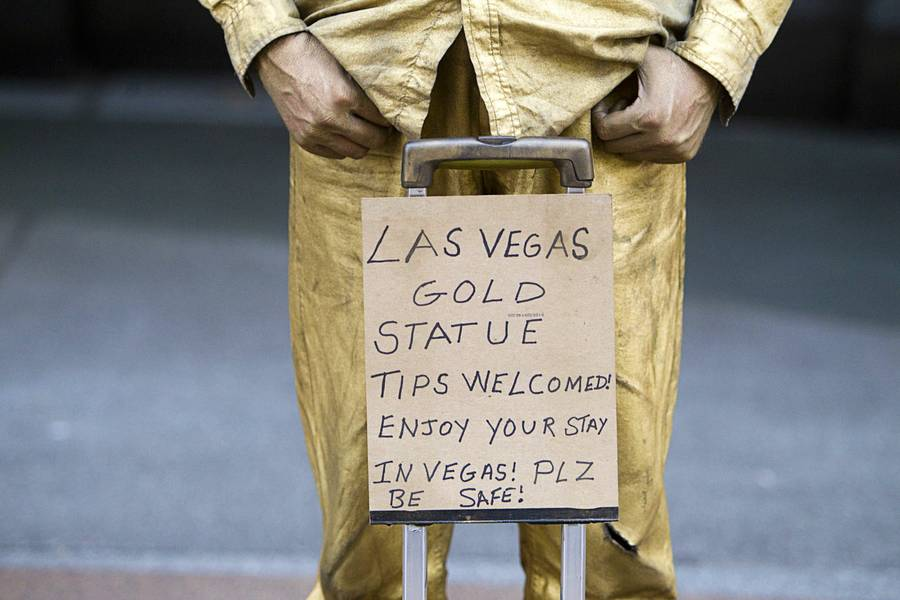 """Las Vegas Gold Statue"" Steve McDonald stands behind a sign at Fremont Street Experience on Sunday, July 27, 2014, in downtown Las Vegas."