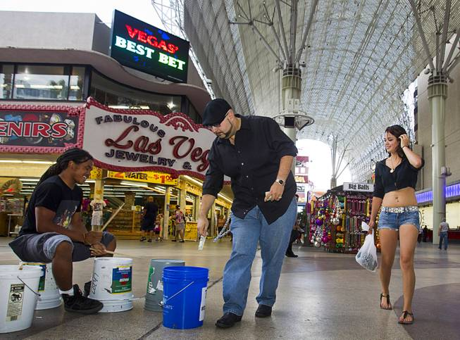 Chris Torres and Yvonne Armijo of Socorro, N.M., tip drummer JaRed Crawford, 17, a Las Vegas Academy senior, at the Fremont Street Experience Sunday, July 27, 2014.