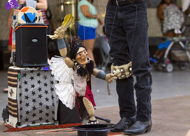 A marionette is brought to life by Buddy Big Mountain at the Fremont Street Experience Sunday, July 27, 2014.