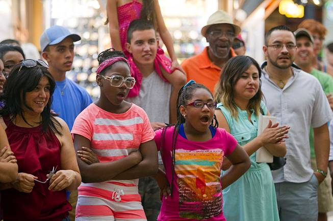 People watch a magician at the Fremont Street Experience Sunday, July 27, 2014.