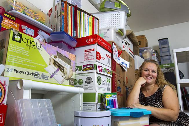 Kindergarten teacher Christine Cordova sits among school supplies stacked against a wall in the garage of her home in Henderson Sunday, July 27, 2014. Cordova rented a 19-foot U-Haul to pack up her classroom supplies from her old school as she prepares to move into a new school in the fall.
