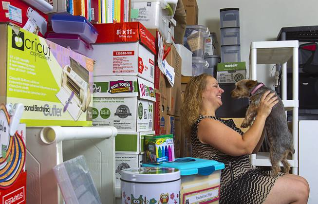 Kindergarten teacher Christine Cordova holds her dog Cookie, a three-year-old silky terrier, by school supplies stacked against a wall in the garage of her home in Henderson Sunday, July 27, 2014. Cordova rented a 19-foot U-Haul to pack up her classroom supplies from her old school as she prepares to move into a new school in the fall.