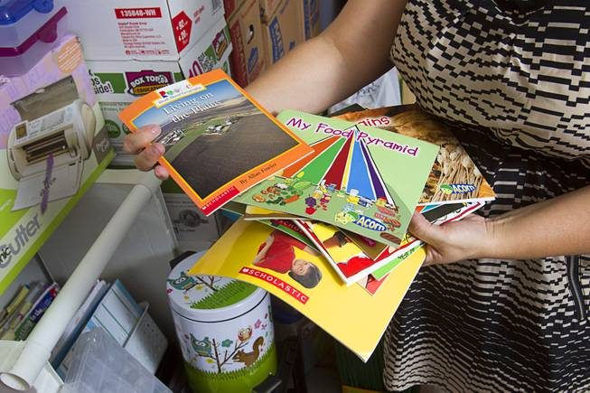 Books purchased by kindergarten teacher Christine Cordova are displayed in the garage of her home in Henderson Sunday, July 27, 2014. Cordova rented a 19-foot U-Haul to pack up her classroom supplies from her old school as she prepares to move into a new school in the fall.
