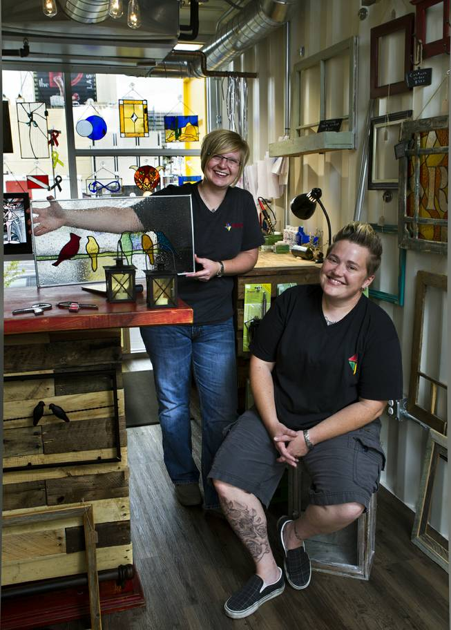 (From front) Owners Mya Daily and Ellisha Haddix of stained glass business Lead In the Window within their Container Park shop on Friday, July 25, 2014.