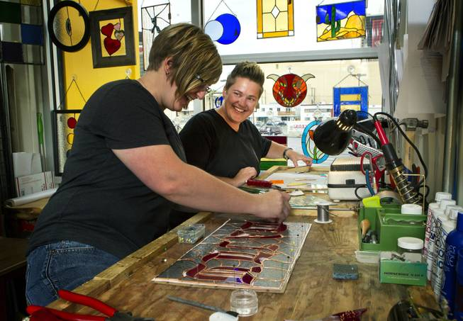 Owners Ellisha Haddix and Mya Daily of stained glass business Lead In the Window work on their current pieces within Container Park on Friday, July 25, 2014.