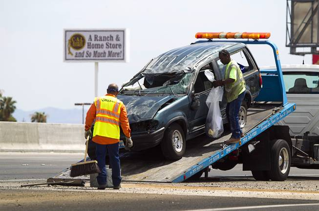 Tow truck drivers clean up after a fatal rollover on Highway 95 southbound at Jones Boulevard Monday, July 28, 2014. A 48-year-old man was ejected from the vehicle and died at the hospital.