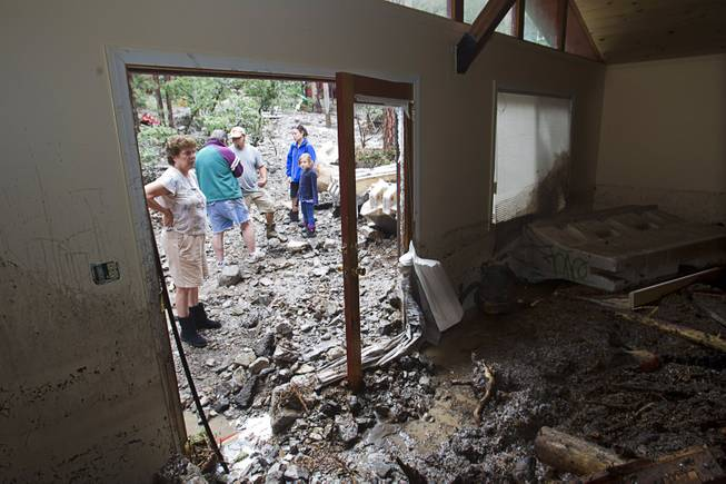 Resident Joyce Luman looks inside a neighbor's home in the Rainbow Subdivision on Mt. Charleston Monday, July 28, 2014. The homeowners were still repairing the home from last year's storm, neighbors said.