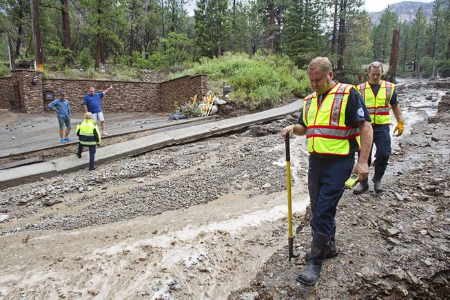 Firefighters inspect damage to Rainbow Canyon Boulevard in the Rainbow Subdivision on Mt. Charleston Monday, July 28, 2014. The neighborhood was hit hard by flooding and debris in runoff last year as well.