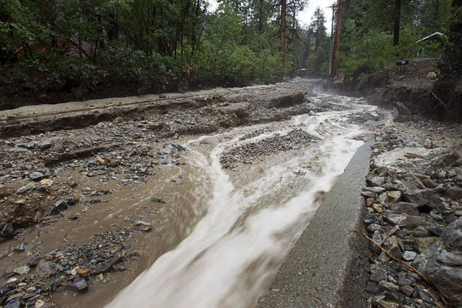 Storm runoff flows down Rainbow Canyon Boulevard in the Rainbow Subdivision on Mt. Charleston Monday, July 28, 2014. The neighborhood was hit hard by flooding and debris in runoff last year as well.