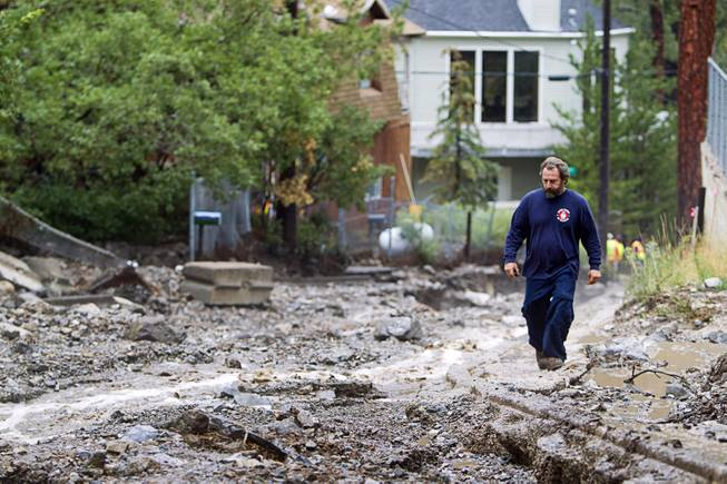 Volunteer firefighter Jim Tiscareno walks up Rainbow Canyon Boulevard in the Rainbow Subdivision on Mt. Charleston Monday, July 28, 2014. The neighborhood was hit hard by flooding and debris in runoff last year as well.