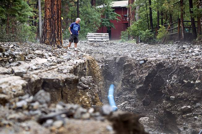 Resident Mike Saulpaw looks over damage to Rainbow Canyon Boulevard in the Rainbow Subdivision on Mt. Charleston Monday, July 28, 2014. The neighborhood was hit hard by flooding and debris in runoff last year as well.