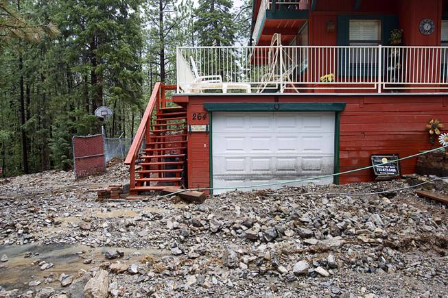 Debris is shown on front of a home in the Rainbow Subdivision on Mt. Charleston Monday, July 28, 2014. The neighborhood was hit hard by flooding and debris in runoff last year as well.