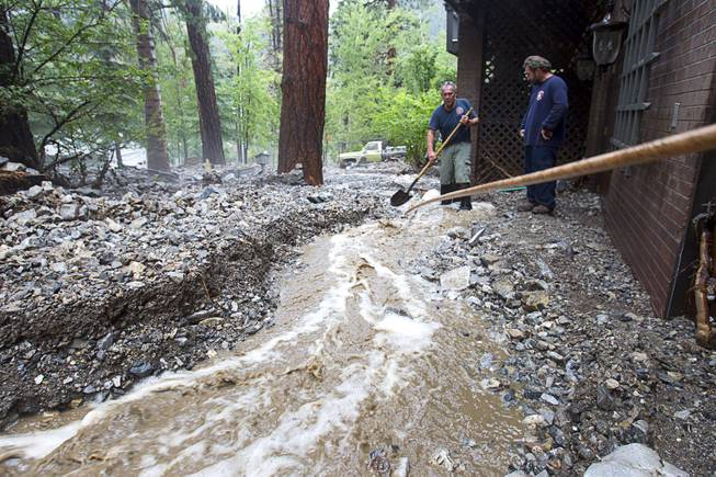 Duffy Grismanauskas, left, talks with volunteer firefighter Jim Tiscareno as he tries to keep runoff from his home in the Rainbow Subdivision on Mt. Charleston Monday, July 28, 2014. The neighborhood was hit hard by flooding and debris in runoff last year as well.