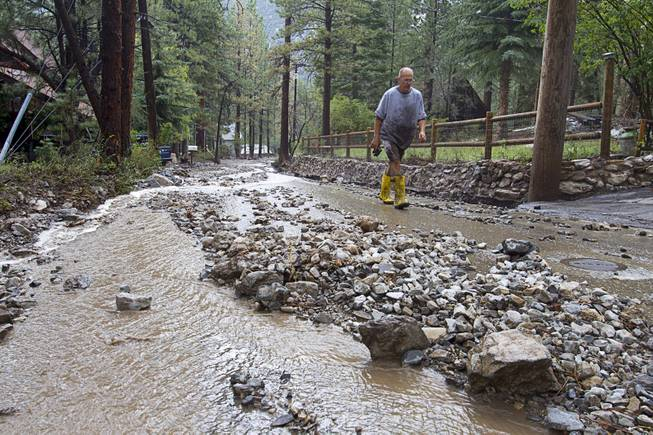 Resident Steve Kammer walks along Rainbow Canyon Boulevard in the Rainbow Subdivision on Mt. Charleston Monday, July 28, 2014. The neighborhood was hit hard by flooding and debris in runoff last year as well.