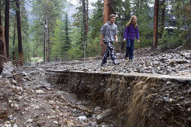 Residents Austin Thomas, 15, and Reznor Weist, 13, walk along a flood-damaged Rainbow Canyon Boulevard in the Rainbow Subdivision on Mt. Charleston Monday, July 28, 2014. The neighborhood was hit hard by flooding and debris in runoff last year as well.