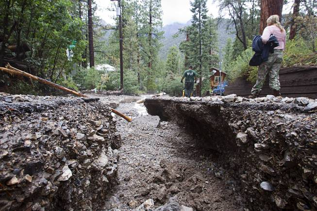 Resident Lynn Thomas, right, walks along a flood-damaged Rainbow Canyon Boulevard in the Rainbow Subdivision on Mt. Charleston Monday, July 28, 2014. The neighborhood was hit hard by flooding and debris in runoff last year as well.
