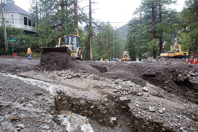 Work crews start repairs to Rainbow Canyon Boulevard in the Rainbow Subdivision on Mt. Charleston Monday, July 28, 2014. The neighborhood was hit hard by flooding and debris in runoff last year as well.