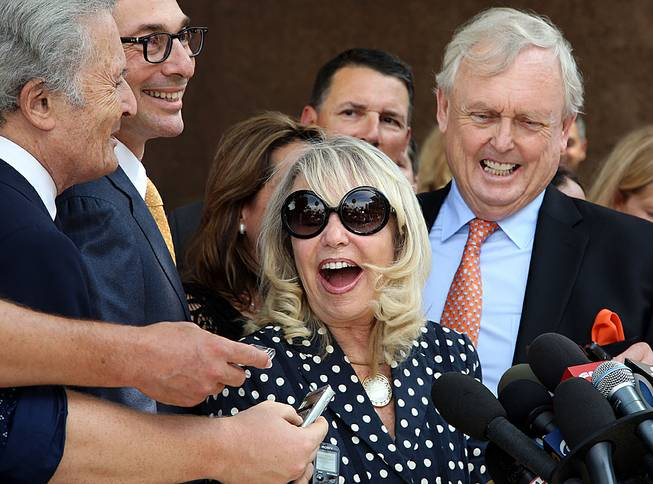 With her attorney Pierce O'Donnell, right, Shelly Sterling, center, talks to reporters after a judge ruled in her favor and against her estranged husband, Los Angeles Clippers owner Donald Sterling, in his attempt to block the $2 billion sale of the NBA basketball team, outside Los Angeles Superior Court, Monday, July 28, 2014.