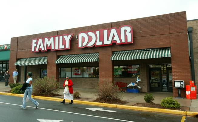 In this Tuesday, Nov. 29, 2005, file photo, customers walk past a Family Dollar store at Hickory Grove Market in Charlotte, N.C. Dollar Tree is buying rival discount store Family Dollar in a cash-and-stock deal valued at about $8.5 billion, the companies announced Monday, July 28, 2014.