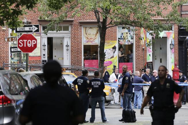 Police officers stand guard at the scene of a shooting, Monday, July 28, 2014, in the Greenwich Village neighborhood in New York. Authorities said a sex-assault suspect got in a shootout with law enforcement in New York City that left the suspect dead and two federal marshals and a police officer wounded.