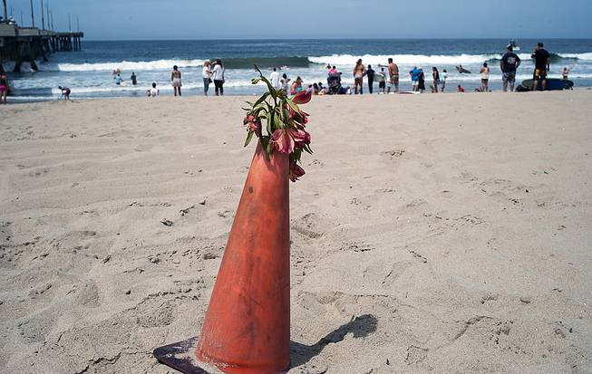 A bouquet of flowers is set on a warning cone at the Venice Beach pier in Los Angeles, Monday, July 28, 2014. Los Angeles' popular Venice Beach teemed with people enjoying a weekend outing on the boardwalk and sand when lifeguards and other witnesses say lightning from a rare summer thunderstorm hit without warning, injuring or rattling more than a dozen people and leaving a 21-year-old man dead.
