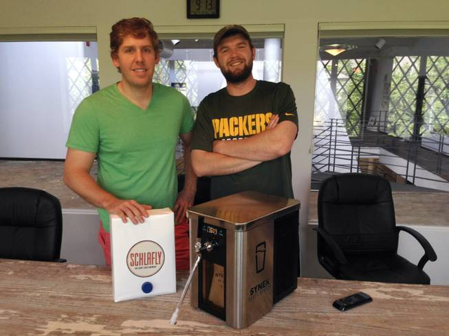 "Synek's co-founder Steve Young, left, and Strategic Director Michael Werner show their ""Keurig machine for beer,"" for which a successful Kickstarter campaign has seen them raise more than $648,000 for development, manufacturing and marketing expenses."