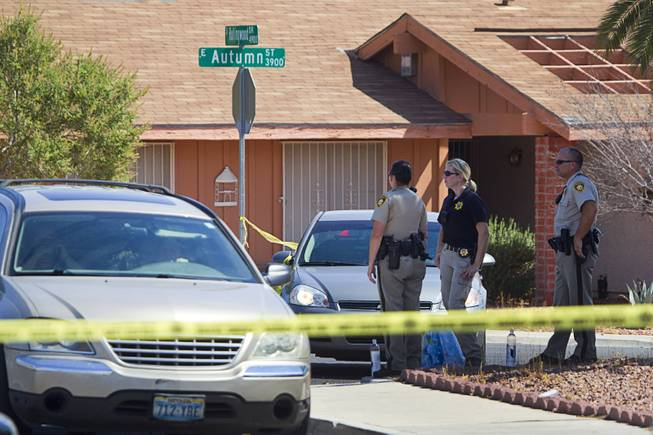 Metro Police officers are shown in a neighborhood near Tropicana Avenue and Sandhill Road after an officer-involved shooting Tuesday, July 29, 2014. The shooting was related to a home invasion, according to Metro Police.