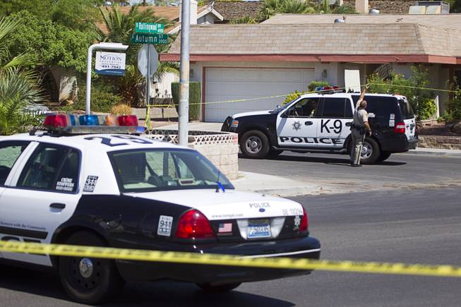 A Metro Police officer lifts crime scene tape over a K9 SUV in a neighborhood near Tropicana Avenue and Sandhill Road after an officer-involved shooting Tuesday, July 29, 2014. The shooting was related to a home invasion, according to Metro Police.