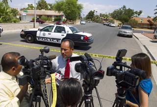 Metro Police public information officer Jose Hernandez speaks to Spanish-language reporters in a neighborhood near Tropicana Avenue and Sandhill Road after an officer-involved shooting Tuesday, July 29, 2014.