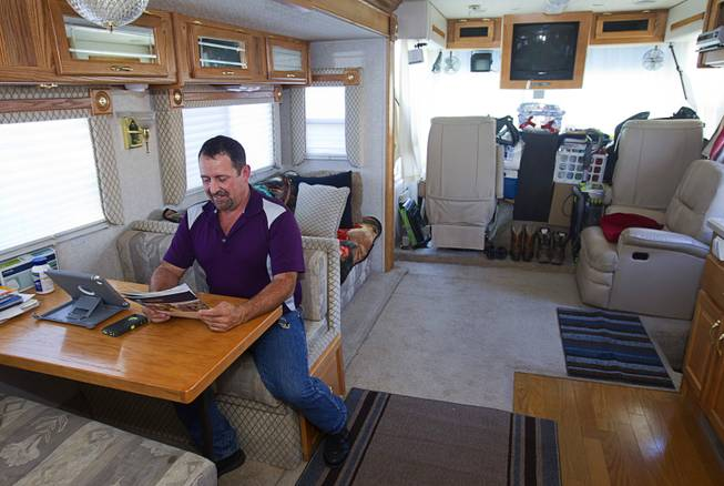 Cass Via, a maintenance worker at the High Roller, looks over a home listing in his RV at the Oasis Las Vegas RV Resort Tuesday, July 29, 2014. Via is in the market for a house but says he will be buying a pre-owned home, not a new one.