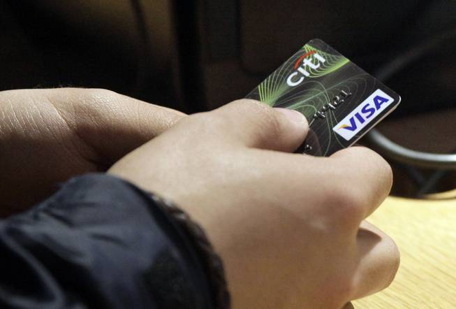 In this May 9, 2012, file photo, a Visa credit card is tendered at the opening of the Superdry store in New York's Times Square. More than 35 percent of Americans have debts and unpaid bills that have been reported to collection agencies, according to a study released Tuesday, July 29, 2014, by the Urban Institute.