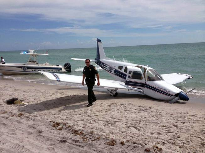 This Sunday, July 27, 2014, photo provided by the Sarasota County Sheriff's Office shows emergency personnel at the scene of a small plane crash in Caspersen Beach in Venice, Fla.