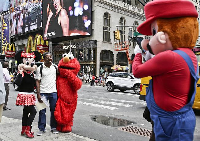 A visitor to Times Square stands for photos with costumed characters Monday, July 28, 2014, in New York. New York Mayor Bill de Blasio said Monday that he believes the people wearing character costumes in Times Square should be licensed and regulated.