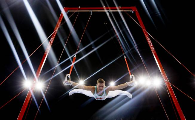 Lights flare as Harry Owen of Wales performs on the rings during the Men's All-Around gymnastics competition at the Scottish Exhibition Conference Centre during the Commonwealth Games 2014 in Glasgow, Scotland, Wednesday July 30, 2014.