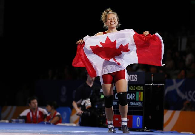 Gold medalist Dori Yeats of Canada celebrates waving the national flag of Canada after defeating Angele Tomo of Cameroon in their gold medal women's 69 kg wrestling bout at the Commonwealth Games Glasgow 2014, in Glasgow, Scotland, Wednesday, July, 30, 2014.