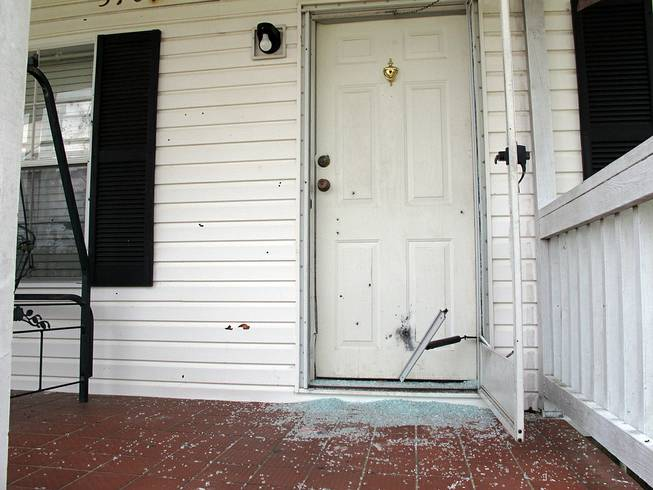 The front door of a home is riddled with bullet holes in Fayetteville, N.C., on Wednesday, July 30, 2014. An angry husband sprayed his father-in-law's house with bullets from two 30-round magazines, killing two people.