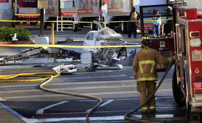 The wreckage of a small plane sits in the parking lot of shopping center Wednesday afternoon, July 30, 2014, in San Diego. Police said that one woman was killed and one hurt in the crash.