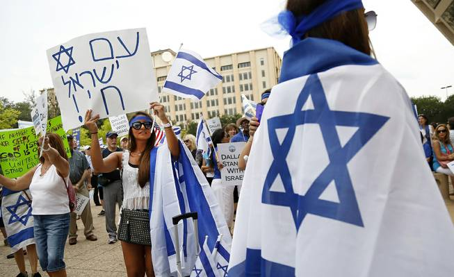 Rebecca Abramov, second from left, holds up a sign in Hebrew during a rally in support of Israel in front of city hall in Dallas, Texas, Wednesday, July 30, 2014.