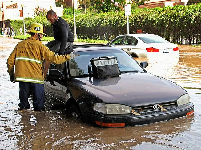 A Los Angeles firefighter helps a driver whose car became stranded on Sunset Boulevard after a 30-inch water main broke and sent water flooding down Sunset and onto the UCLA campus in the Westwood section of Los Angeles Tuesday, July 29, 2014.