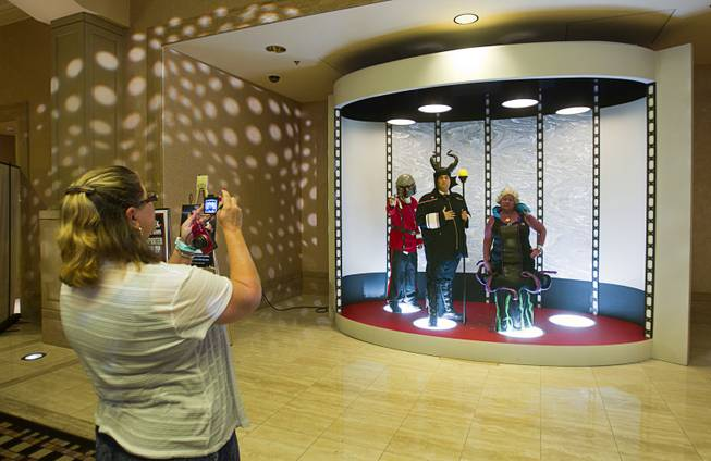 Fans have their photo taken in a mock transporter during the 13th annual Official Star Trek Convention at the Rio Thursday, July 31, 2014. From left are: Jim Cartwright of Hesperia, Calif., Chris Dickson of Costa Mesa, Calif. and Donna Long of Hesperia, Calif.