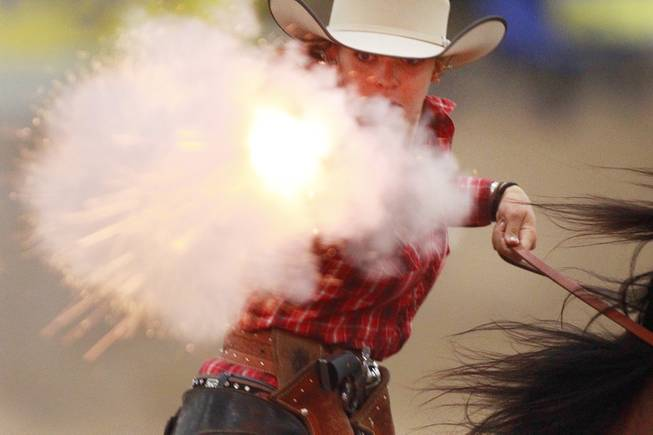 Breanna Coston fires at a target during the Cowboy Mounted Shooting Association's Western U.S. ChampionshipThursday, July 31, 2014 at the South Point.