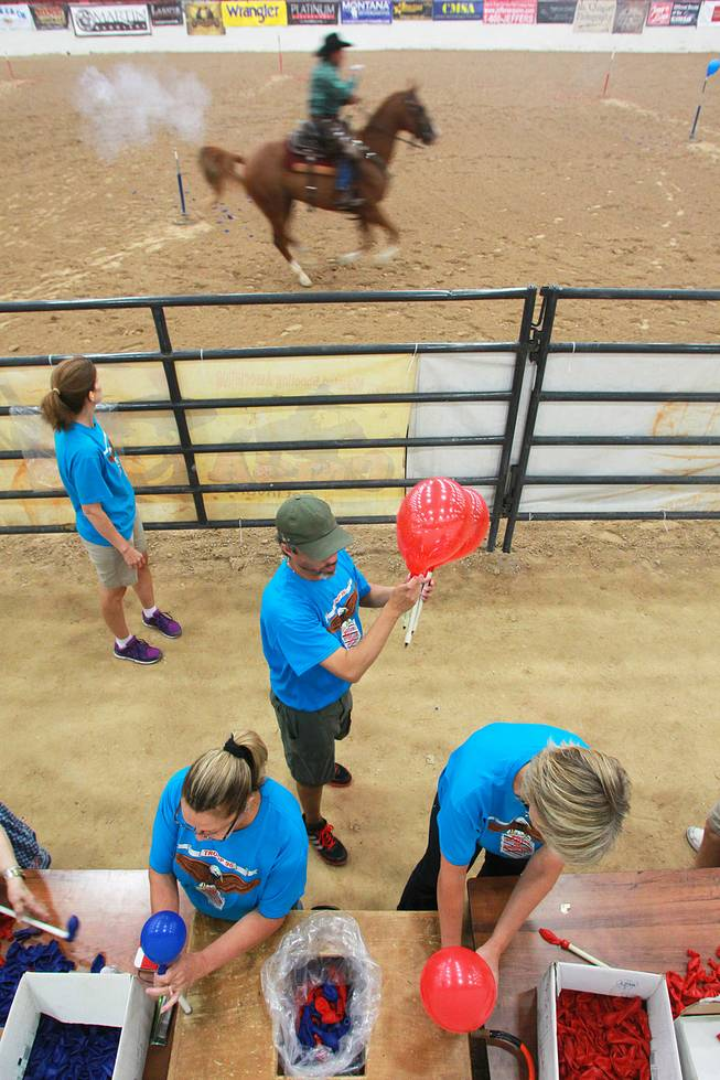 Volunteers fill target balloons as a cowboy competes during the Cowboy Mounted Shooting Association's Western U.S. ChampionshipThursday, July 31, 2014 at the South Point.