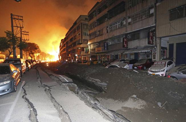 Tossed vehicles line an destroyed street as flames continue to burn from multiple explosions from an underground gas leak in Kaohsiung, Taiwan, early Friday, Aug. 1, 2014. A massive gas leakage early Friday caused five explosions that killed several people and injured over 200 in the southern Taiwan port city of Kaohsiung.