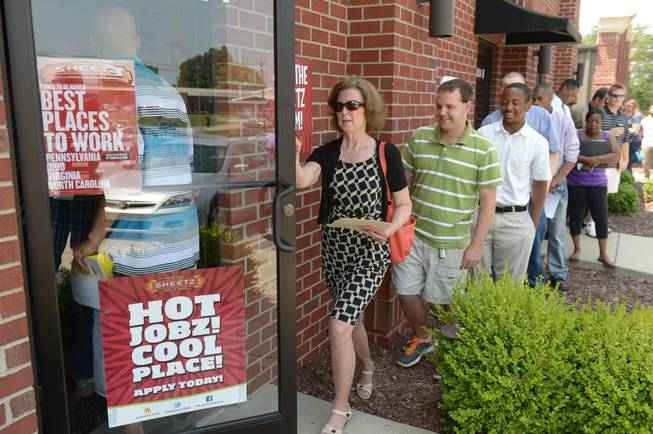 In this Wednesday, June 18, 2014, photo, job seekers attend a job fair held by Sheetz to staff their under-construction distribution center, in Burlington, N.C. As the economic recovery enters its sixth year, many Americans don't feel better off.