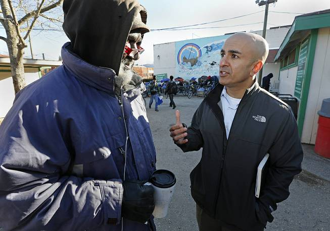 In this Dec. 4, 2013 file photo, Neel Kashkari, right, who later won the Republican nomination for governor of California, talks with Kenneth Whitaker, 62, at Loaves and Fishes homeless shelter in Sacramento, Calif.