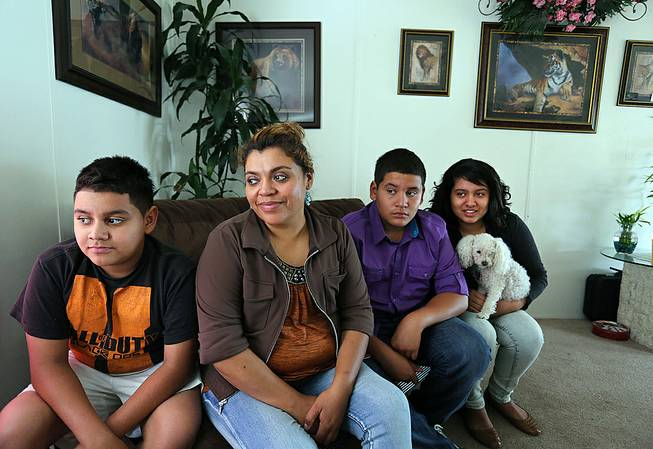 Adriana Gaytan, who came to Colorado in 1997 from the Mexican state of Zacatecas, second from left, sits at home with her children who were born in the U.S. from left to right, Osbaldo, 11, Oscar 13, Indhira, 14, and their dog Kissy, in Aurora, Colo., Thursday, July 31, 2014. Gaytan will get a driver's license soon, as Colorado will begin issuing driver's licenses and identification cards to people who are in the country illegally or have temporary legal status.